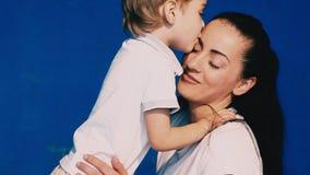 Il gioco del figlio e della madre ride e bacia su un fondo blu video d archivio