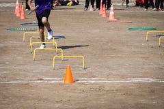 Il gioco della corsa funziona attraverso gli ostacoli nella scuola immagini stock