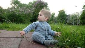 Il gioco divertente adorabile del bambino al campo da giuoco nell'ambito di cura dei suoi pantaloni a vita bassa parents archivi video