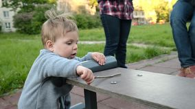 Il gioco divertente adorabile del bambino al campo da giuoco nell'ambito di cura dei suoi pantaloni a vita bassa parents video d archivio