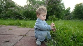Il gioco divertente adorabile del bambino al campo da giuoco nell'ambito di cura dei suoi pantaloni a vita bassa parents stock footage