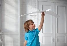Il gioco felice del ragazzo con l'aeroplano a disposizione, bambino sogna del traveli Fotografia Stock