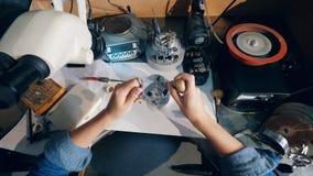 Il gioielliere utilizza la lente di ingrandimento del gioielliere mentre lavora con un grande anello video d archivio