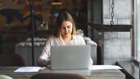 Il giornalista femminile formalmente vestito del positivo che fa il lavoro distante durante il lavoro irrompe l'interno del caffè