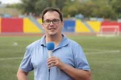 Il giornalista sta riferendo dallo stadio Immagine Stock Libera da Diritti