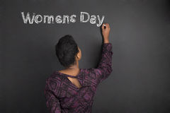 Il giorno afroamericano delle donne di scrittura dell'insegnante della donna sul fondo del bordo del nero del gesso Fotografia Stock Libera da Diritti