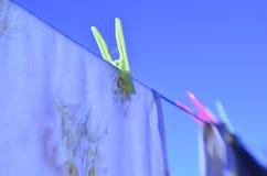 Il giorno della lavanderia copre sulle mollette per il bucato variopinte della corda da bucato contro cielo blu Fotografia Stock Libera da Diritti