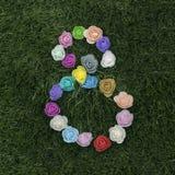 Il giorno delle donne internazionali 8 marzo simbolo con i fiori su erba Immagini Stock Libere da Diritti