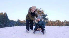 Il giorno di inverno, la giovane donna felice spinge il figlio sulla slitta dalla collina nevosa e funziona dopo lui al rallentat video d archivio