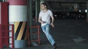 Il giovane è corrente e nascondentesi dietro la colonna sul parcheggio sotterraneo Movimento lento stock footage