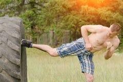 Il giovane è dato dei calci a un piede in una gomma workout fotografie stock