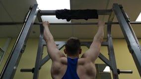 Il giovane è impegnato nella forma fisica nella palestra L'atleta è tirato su sulla barra