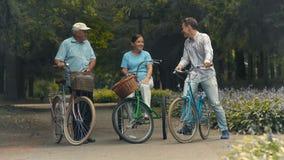 Il giovane accoglie le coppie senior sulle biciclette in parco video d archivio