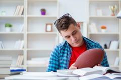 Il giovane adolescente che prepara per gli esami che studiano ad uno scrittorio all'interno Immagine Stock Libera da Diritti