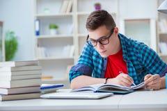 Il giovane adolescente che prepara per gli esami che studiano ad uno scrittorio all'interno Fotografie Stock