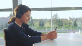 Il giovane adolescente felice in cuffie che ascolta lo stile di vita di musica sulla chiacchierata dello smartphone comunica in archivi video