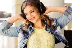 Il giovane adolescente felice sta indossando le cuffie Immagine Stock