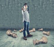 Il giovane adolescente rompe i pezzi degli scacchi Immagini Stock