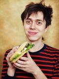 Il giovane affamato mangia un hamburger Immagini Stock