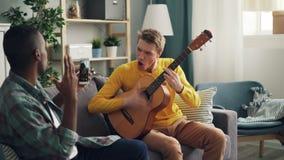 Il giovane afroamericano sta tenendo lo smartphone moderno e sta facendo il video del suo amico caucasico che gioca la chitarra e archivi video