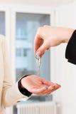 Il giovane agente immobiliare è con i tasti in un appartamento Fotografia Stock