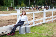 Il giovane agricoltore adulto sveglio della ragazza, sedentesi sopra può dopo lavoro Grande latta due con latte Pausa dopo lavoro Fotografia Stock Libera da Diritti