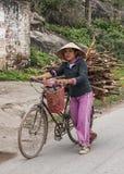 Il giovane agricoltore femminile cammina bici caricata con il legno del fuoco Fotografia Stock Libera da Diritti