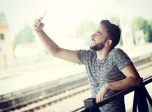 Il giovane alla stazione ferroviaria prende un selfie Immagini Stock Libere da Diritti