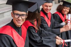 Il giovane allegro che celebra la graduazione con il suo gruppo si accoppia Immagini Stock Libere da Diritti