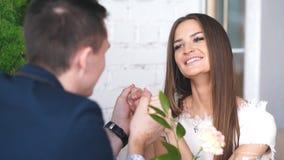 Il giovane allegro e la donna stanno datando nel ristorante Stanno sedendo alla tavola e stanno esaminandose con amore video d archivio