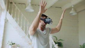 Il giovane allegro si diverte e balla mentre ottiene l'esperienza facendo uso di 360 vetri della cuffia avricolare di VR di realt fotografia stock