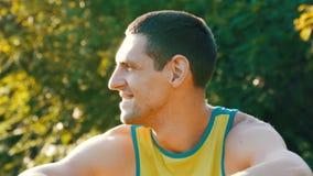 Il giovane allegro si siede su un'erba verde di estate e sorride archivi video