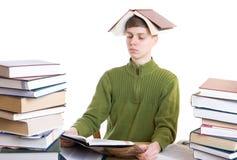 Il giovane allievo con i libri isolati su un bianco Immagini Stock