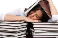 Il giovane allievo faticoso è sotto e sopra i libri Fotografie Stock Libere da Diritti