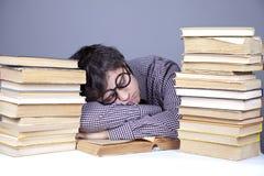 Il giovane allievo faticoso con i libri ha isolato. Fotografia Stock