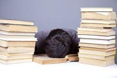 Il giovane allievo faticoso con i libri ha isolato. Immagini Stock