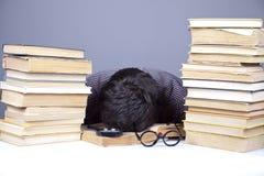 Il giovane allievo faticoso con i libri ha isolato. Immagine Stock