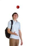 Il giovane allievo getta in su la mela rossa Immagini Stock