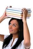 Il giovane allievo impara una pila di libri sulla testa Fotografia Stock