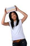 Il giovane allievo impara una pila di libri sulla testa Immagini Stock