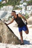 Il giovane allungamento bello dell'uomo di sport risolve alla spiaggia Immagine Stock