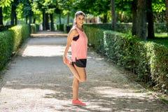Il giovane allungamento femminile latino attraente prima di lei risolve il funzionamento in un parco moderno Immagine Stock Libera da Diritti