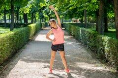 Il giovane allungamento femminile latino attraente prima di lei risolve il funzionamento in un parco moderno Immagini Stock Libere da Diritti