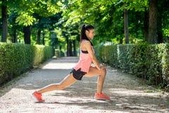 Il giovane allungamento femminile latino attraente prima di lei risolve il funzionamento in un parco moderno Immagine Stock