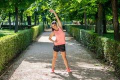 Il giovane allungamento femminile latino attraente prima di lei risolve il funzionamento in un parco moderno Fotografia Stock