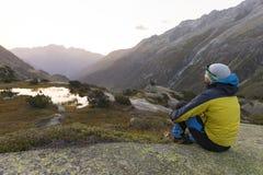 Il giovane alpinista gode dei raggi di sole di riscaldamento dopo che un giro rigoroso della montagna Fotografia Stock