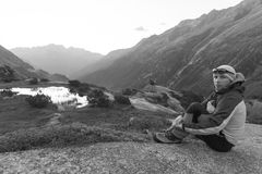 Il giovane alpinista gode dell'alba dopo che un giro rigoroso della montagna Immagine Stock Libera da Diritti
