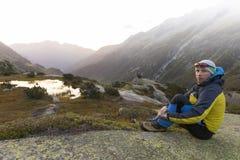 Il giovane alpinista gode dell'alba dopo che un giro rigoroso della montagna Immagine Stock