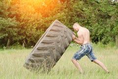 Il giovane alza la gomma workout fotografia stock libera da diritti
