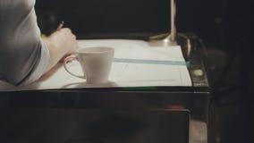 Il giovane architetto lavora in un ufficio moderno Tazza della bevanda nel posto di lavoro video d archivio
